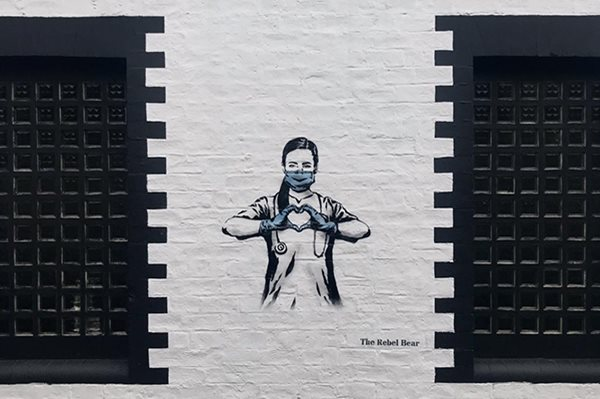 Street art by The Rebel Bear depicting a nurse in black and white with a blue face mask and gloves, with her hands making the shape of a heart.
